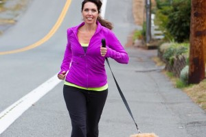 A pretty woman running with a golden retriever dog in the street