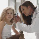 Caucasian doctor examining ear of girl