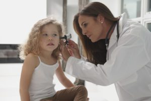 Caucasian doctor examining ear of girl