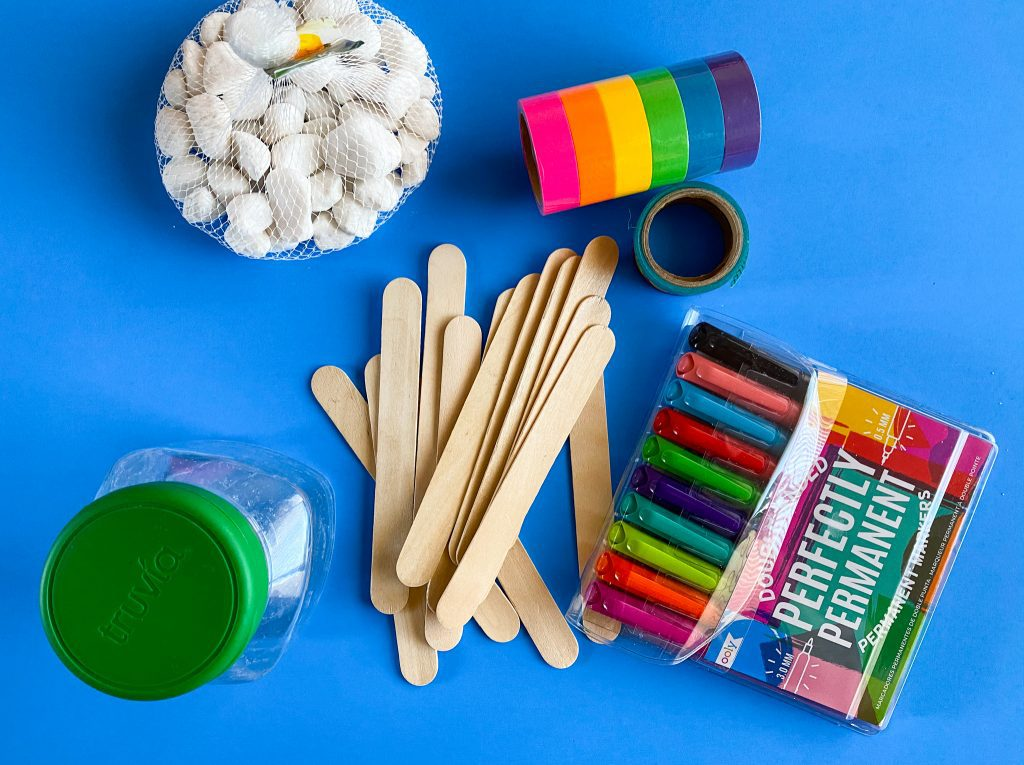 DIY items such as rocks, washi tape, popsicle sticks, a container and markers