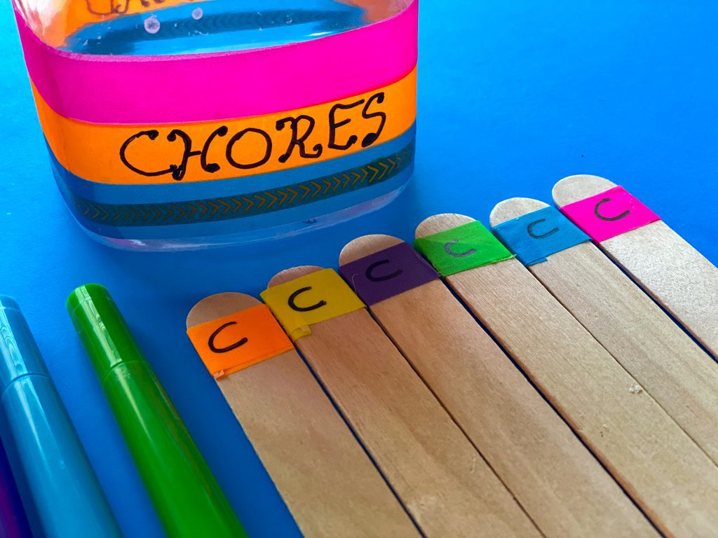 sticks with colored washi tape in front of a reward jar that says chores